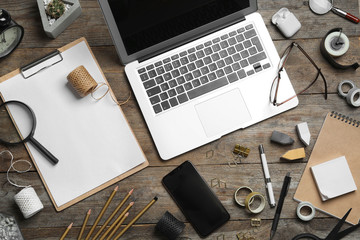 Flat lay composition with laptop, smartphone and stationery on wooden table. Designer's workplace