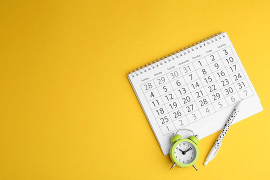 Calendar, pen and alarm clock on yellow background, flat lay. Space for text