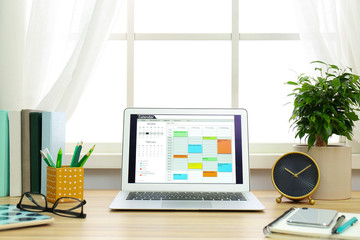 Modern laptop with calendar on screen in office Wall mural