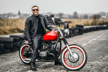 Red motorbike with rider. A man in a black leather jacket and pants stands sideways in the middle...