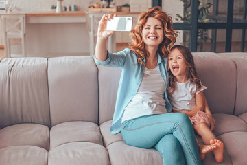 mother and daughter taking selfie on smartphone at home