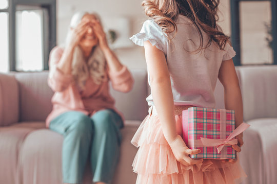 girl holding present box in the hands behind her back and making surprise for grandmother sitting on the couch