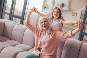 happy grandmother sitting on the sofa and holding grandaughters hands in living room