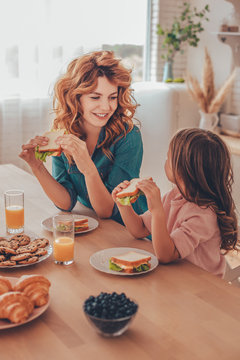 mother and daughter eating sandwiches for breakfast and looking at each other at the kitchen