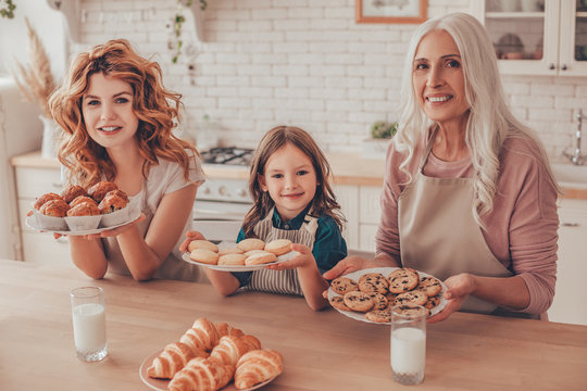 girl, mother and grandmother holding freshly baked cookies products on the plates and looking at the camera
