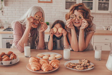 girl, mother and grandmother covering eyes with cookies sitting at the kitchen table together