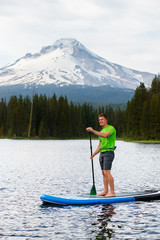 A man paddles on a stand up paddleboard at Trillium Lake, a popular recreation spot near the base of Mount Hood, Oregon.