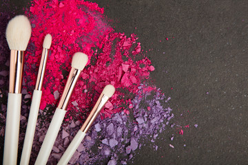 White make up brushes and violet and pink eyeshadows arranged on flat stone