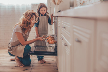 daughter and mother taking croissants from the oven in the kitchen