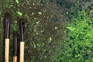 Black make up brushes and green eyeshadows arranged on flat stone