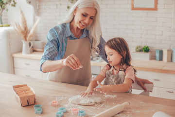 grandmother sprinkling flour on the dough for cookies while granddaughter playing with dough