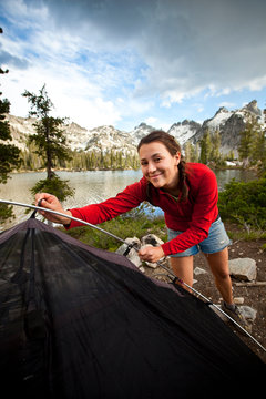 A woman pitches a tent at Alice Lake in the Sawtooth Mountains in Idaho.