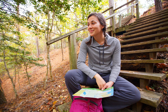 A woman references a trail guide map for the Nags Head Woods Preserve while sitting on a wooden staircase along the Sweetgum Swamp Trail.