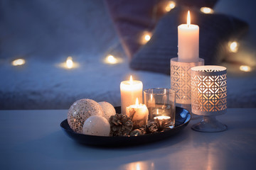 Christmas decoration   with burning candles on  white table against the background of  sofa with...