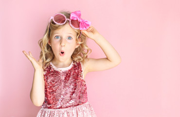 Portrait of a shocked girl wearing pink shiny dress and glasses. Little girl making a surprised expression. Bright and festive background. Party concept.