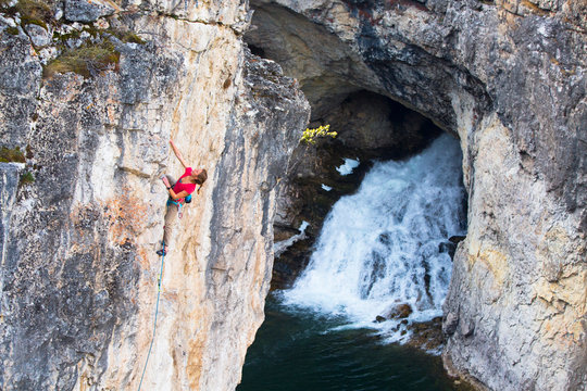 A woman warming up on a beautiful 5.11 sport climb at Natural Bridge State Park. The iconic Natural Bridge Falls is pictured in the background. Normally 100 feet tall, during lower flow times in the summer, fall and early winter the  waters from the Main Boulder River flow into a sinkhole above the falls and come out halfway down the limestone face.