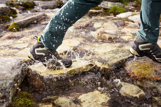 Rondane National Park, Norway: Detail of a male hiker crossing a alpine stream with his Adidas Core-Tex hiking boots.