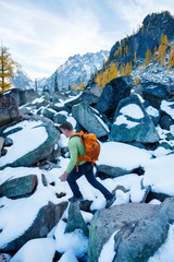 A man with a pack scrambles up a rocky ridge amidst fall colors near Colchuck Lake in the Cascade Range of Washington State.