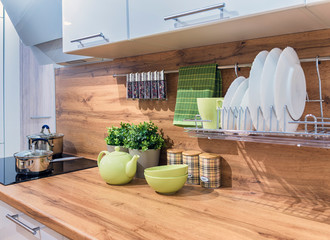 Fragment of the interior of a modern kitchen with white glossy facades, with a wooden tabletop and apron