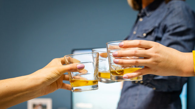 Close up on three female women hands holding a glasses of whiskey or brandy or cognac alcohol drink toasting celebrating at home