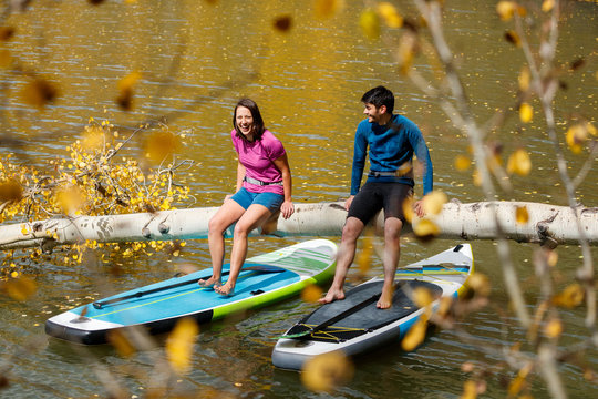 A man and a woman smile while enjoying an afternoon on their inflatable stand up paddle boards while SUPing among the aspen trees in an alpine lake in the San Juan Mountains, Colorado in autumn.