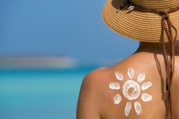 Woman with sun-shaped sun cream on beach
