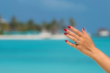 Close up of woman finger showing engagement ring on the tropical beach. Concept of people relationship, ring present, love  and honeymoon at the resort.