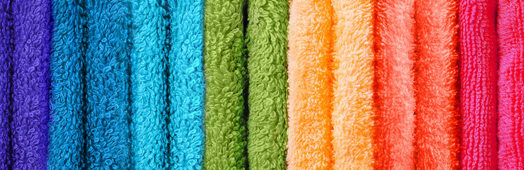 Row of coloured towels folded up vertical image
