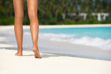 Close-up of female legs in the blue water on the tropical beach. Vacation holidays.