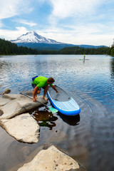 A man prepares to stand up paddleboard at Trillium Lake, a popular recreation spot near the base of Mount Hood, Oregon.