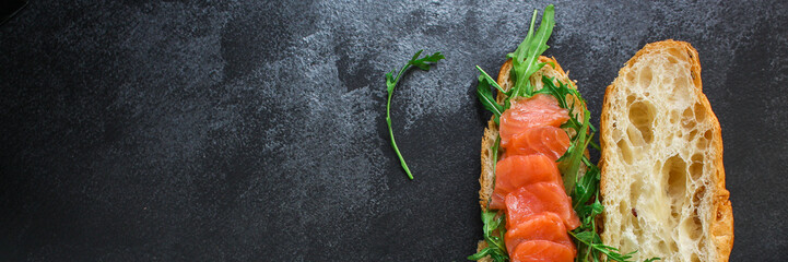 fish sandwich and greens, Smorrebrod (salted salmon, croissant, bread, arugula and other ingredients) menu concept. food background. top view. copy space