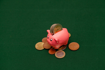 Piggy bank in the form of a pink pig and euro coins and cents on a green background