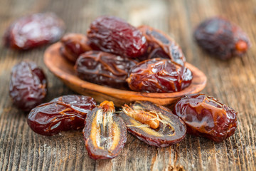 Juicy dates in a bowl on a old wooden table .