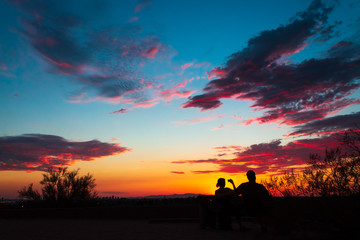 Colorful sky after the sun went down, couple enjoying the scenic nature, taking pictures
