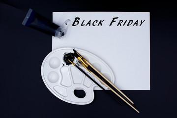 """Farbpalette mit schwarzer Acrylfarbe, Pinseln und Leinwand mit dem Text """"Black Friday"""""""