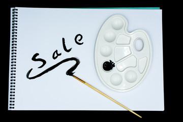 """Farbpalette mit schwarzer Acrylfarbe, Pinsel und Zeichenblock mit dem Text """"Sale"""""""