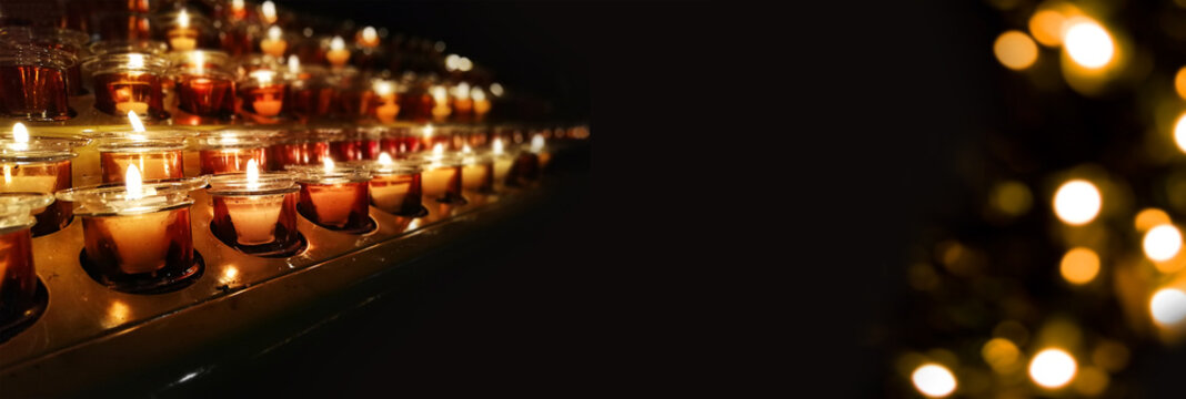 Candles in a church, cathedral or temple, in yellow transparent candlesticks. The concept of mourning. We remember, we grieve. Selective focus, side view, copy space. Banner