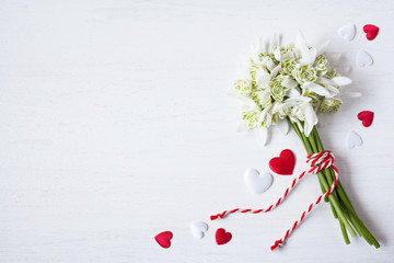 Bouquet of snowdrops and red white hearts on a wooden background for congratulations, holiday Martisor