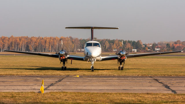 Small two-engine aircraft parked at the airfield