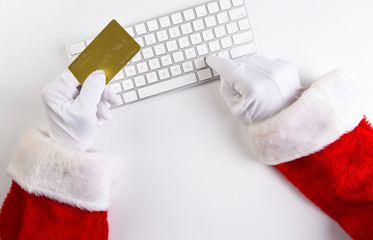 High angle closeup of Santa Claus hands using his computer keyboard to make an online purchase, with his credit card in one hand.