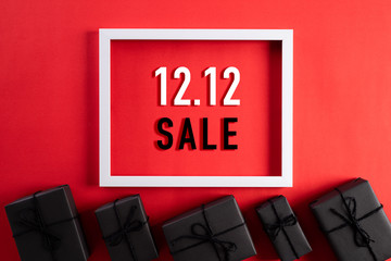 Online shopping of China, 12.12 singles day sale concept. Top view of white picture frame with black gift box on red background with copy space for text 12.12 singles day sale.