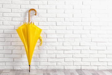 Wall Mural - Beautiful yellow umbrella near white brick wall. Space for text