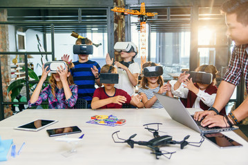 Group of young pupils of elementary school using virtual reality glasses during computer coding...
