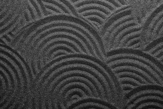 Black sand with beautiful pattern, top view. Zen concept