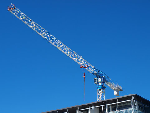 A scenic working Construction Sky Crane on a new high rise multistory building site with a blue sky background. Australia.