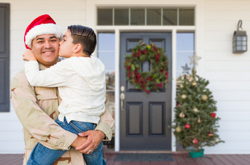 Hispanic Male Soldier Wearing Santa Cap Holding Mixed Race Son In Front of House