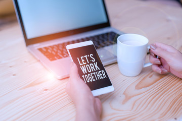 Writing note showing Let S Work Together. Business concept for Unite and Join Forces to Achieve a Common Goal woman with laptop smartphone and office supplies technology
