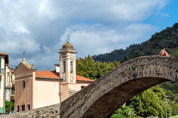 A pretty young woman poses atop the medieval Monet bridge with the Church of San Filippo behind in the historic ancient city of Dolceacqua, Italy.