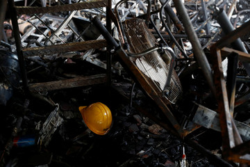A helmet is seen among the remains of a burnt barricade in Hong Kong Polytechnic University (PolyU) in Hong Kong