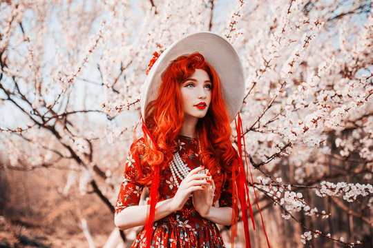 Young handsome redhead girl in spring flower garden. Woman in vintage hat and  retro dress on nature. Beautiful spring cherry tree. Handsome redhead model in retro hat. Vanilla flower dress. Red nails